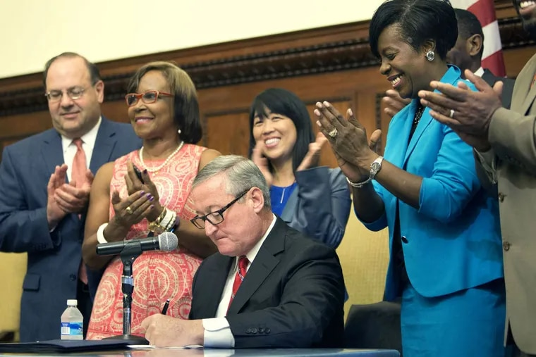 Applause rings out as Mayor Kenney signs the soda-tax bill into law at City Hall in a ceremony in June. The city set up collection and enforcement systems with beverage vendors and distributors, as well as pre-K providers to partner with.
