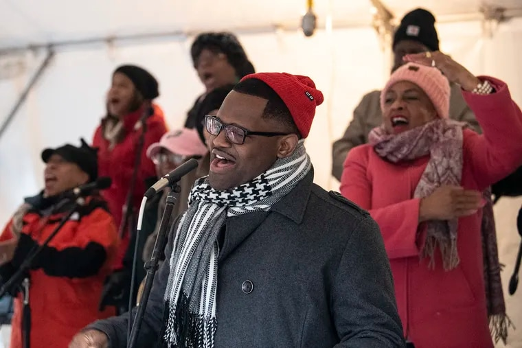 Tyrone Neal sings for marathon participants as they run near the Mother Bethel AME Church at Sixth and Lombard Streets in Philadelphia on Sunday morning.