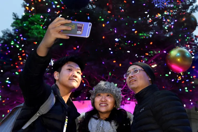 Lena Xu, center, smiles for a holiday selfie at the big Christmas tree outside City Hall in Philadelphia, together with her husband, Kevin Liang, right, and their son Paul, 15.