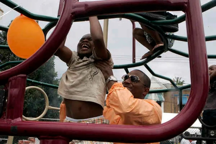 Carl Boddie helps Wayne Styles , 7, with a pull-up on the 2500 block of Napa Street in Strawberry Mansion. Few Good Men held its third annual Father's Day community cookout there yesterday.
