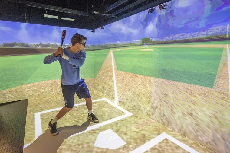 """A Villanova professor developed a program to help Wildcat players improve at the plate. Sam Margulis, a freshman outfielder, demonstrates the virtual reality setup located in """"The Cave"""" in a campus library."""