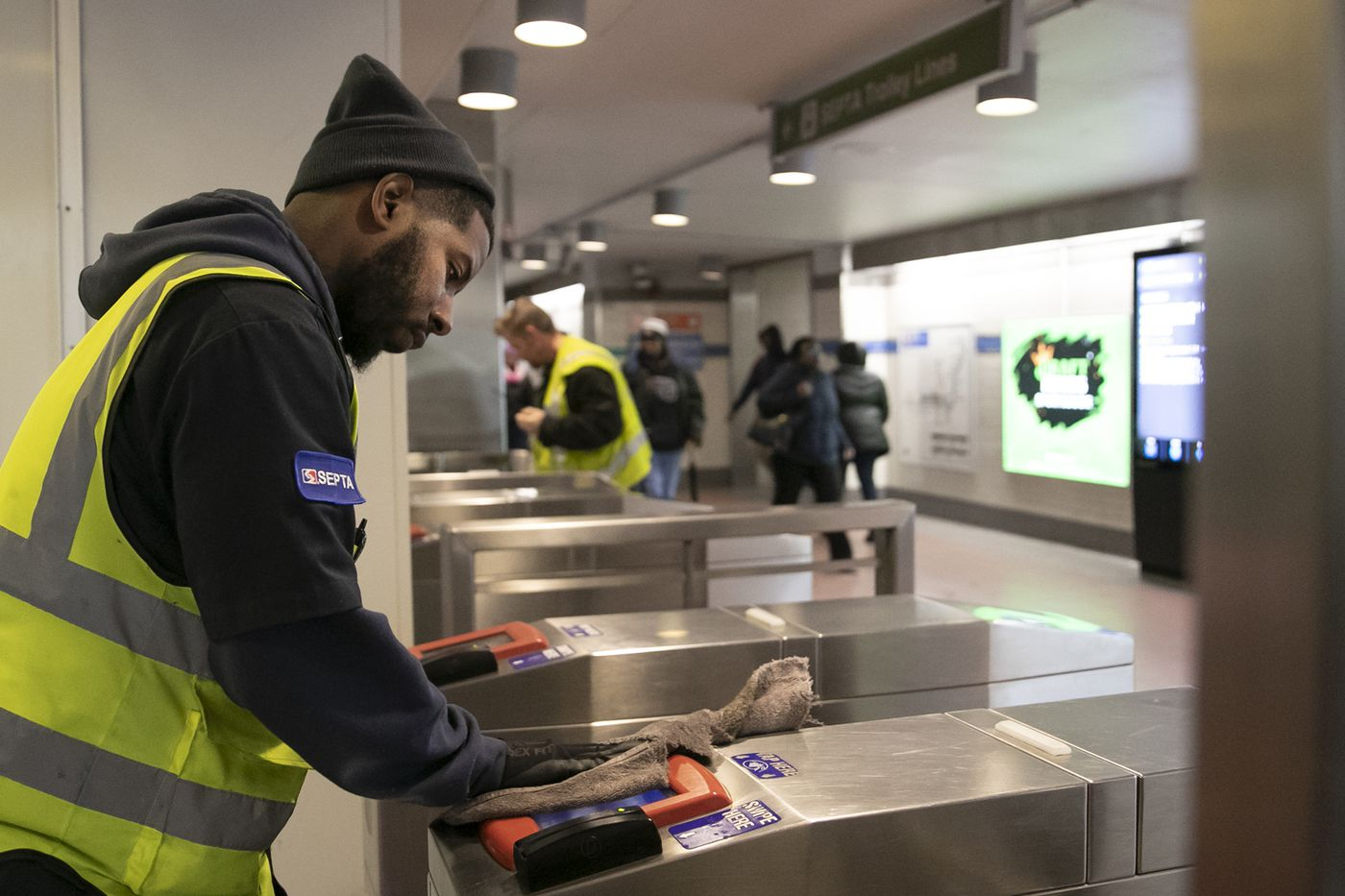 John Mathis, a SEPTA employee, disinfects the turnstiles at the 15th Street Station on the Broad Street Line.