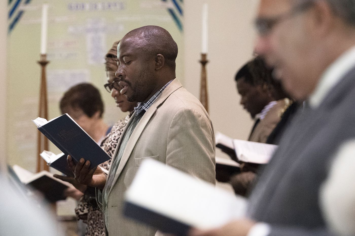 Silva Munuza, center, who emigrated from Cameroon to the United States 10 years ago, prays during Sunday services at St. Paul's Presbyterian Church in Laurel Springs. Munuza is an elder at the church and is working to educate the congregation about the increasingly deadly political violence in his homeland.