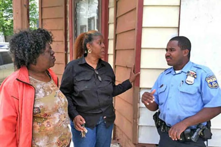 In the Hartranft neighborhood, activists Diane Bridges (left) and Arnetta Curry talk with Police Officer Tyshaan Williams. (Annette John-Hall / Staff)