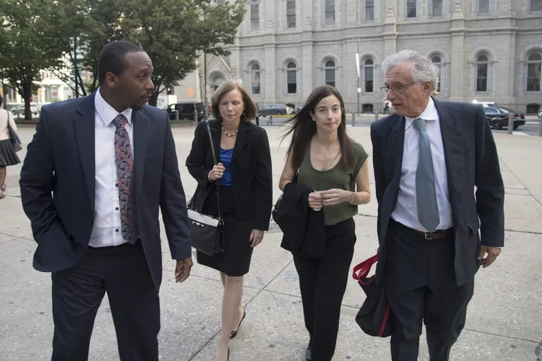 Plaintiff Bryant Miller (left) walks into Philadelphia City Hall in September with lawyers arguing for better school funding in Pennsylvania. The lawyers are Maura McInerney and, Deborah Gordon Klehr of the Education Law Center and Michael Churchill of the Public Interest Law Center.