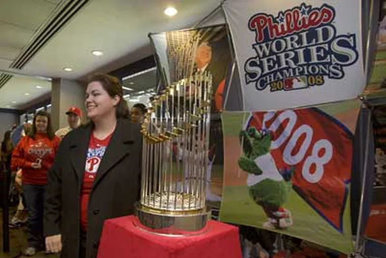 Roxanne Story, of Roselle Park, N.J. poses with the 2008 World Series Trophy at Citizens Bank Park on Sunday. (Ed Hille / Staff Photographer)
