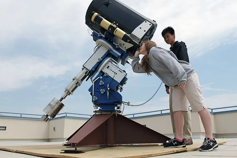 Cecily Sanders, 11th grade, demonstrates the telescope with Anthony Chu, 10th grade, on the roof of the MaST Charter School in Northeast Philadelphia on April 22, 2014. ( DAVID MAIALETTI / Staff Photographer )