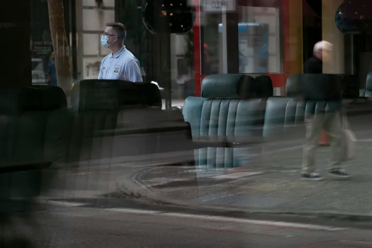 Pedestrians are seen through the glass of an empty Continental Mid-town at 18th and Chestnut Streets in Center City.