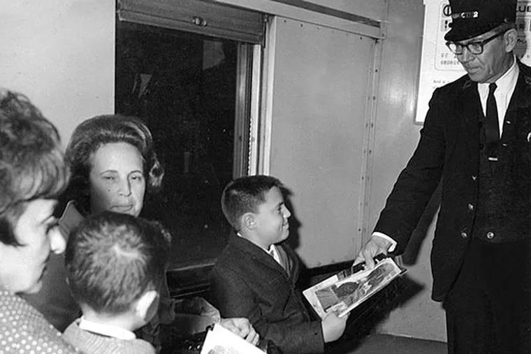 Joseph McKelvie gives a railroad comic book to young Reading rider Frank La Preziosa of Jenkintown.