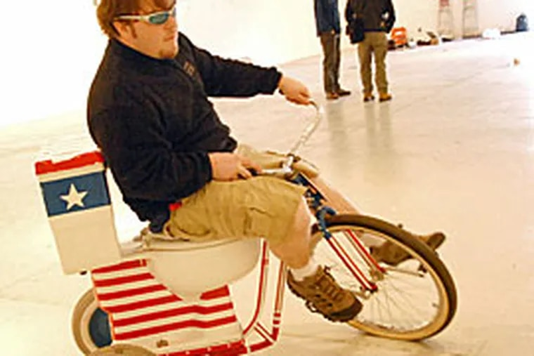 """Justin Dowdall rides a toilet trikes that is part of the """"HeartWorks"""" exhibit in the Ice Box Project Space in Philadelphia. (Peter Tobia/Inquirer)"""