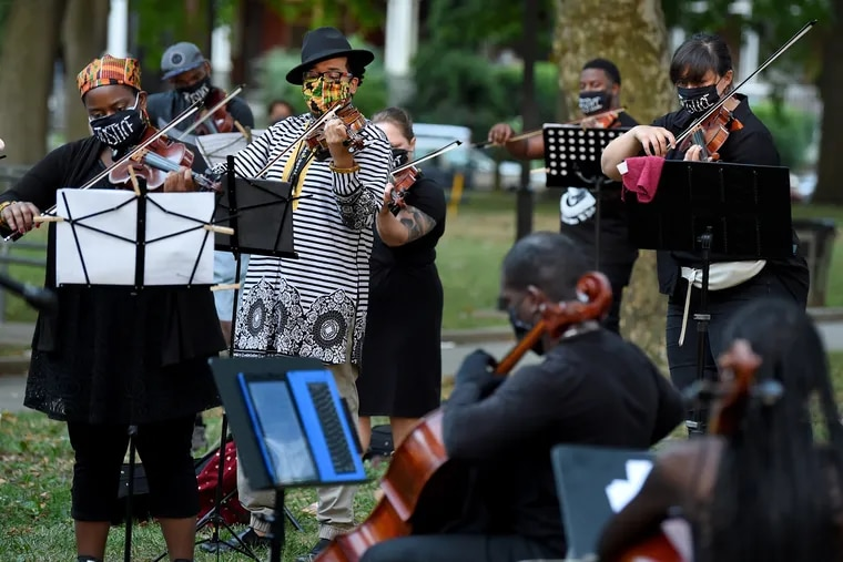 Musicians perform during a candlelight vigil and short concert in memory of Elijah McClain in Malcolm X Park July 15, 2020.
