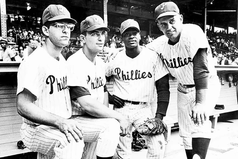 Dick Allen (second from right) stands with Phillies teammates, from left, Cookie Rojas and Johnny Callison, and manager Gene Mauch.
