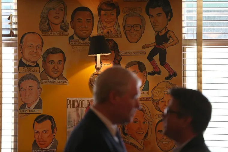 John Dougherty, left, business manager of IBEW Local 98, and councilman Bobby Henon, right, talk in front of some of the caricatures on the wall as they gather for a lunch at The Palm in Philadelphia, Pa. on May 20, 2015.