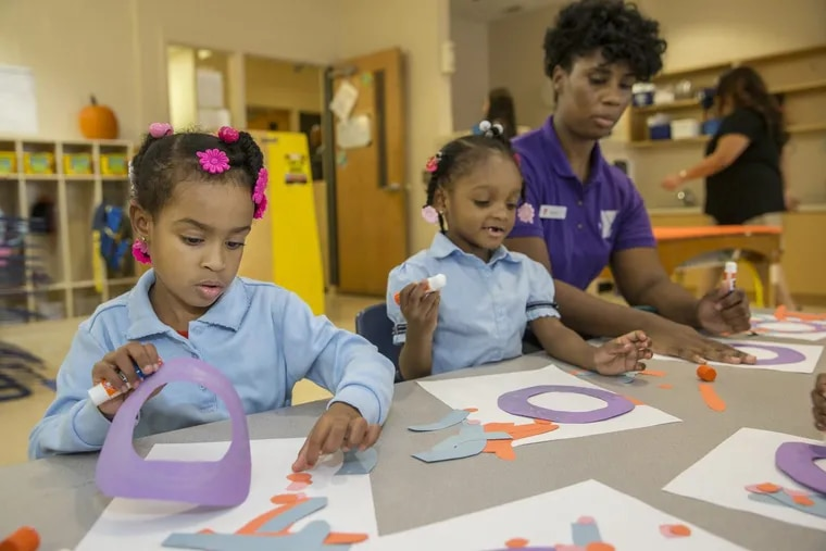 Lyriq Brooks, 4, left, and Ceyanee Brown, center, 4, work with their teacher Shannon Hurley, right, in the Pre-K classroom at the Columbia North YMCA, gluing paper cutouts to make an octopus on October 20, 2016.