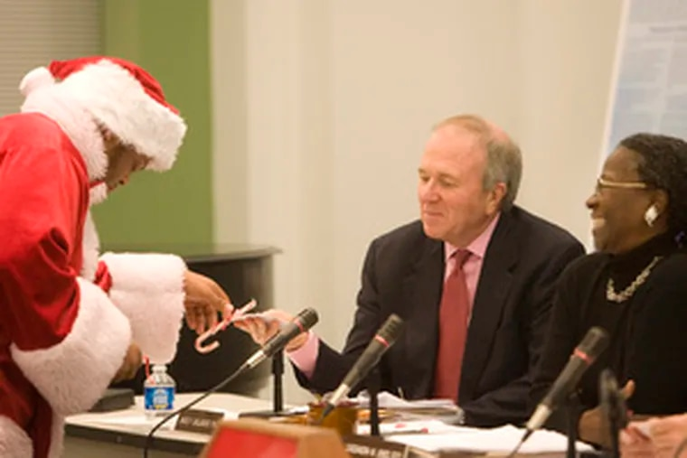 Student Lawrence Jones-Mahoney, dressed as Santa, presents candy canes yesterday to James Gallagher and Cassandra Jones at an SRC meeting, along with a wish list for better schools.