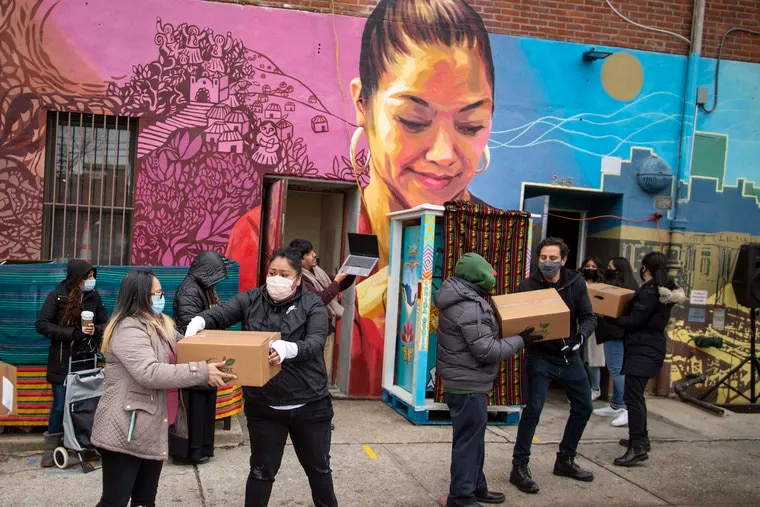 Here in 2021, volunteers carry food for donations as people receive COVID-19 information for vaccines at the community center Mixteca in the Brooklyn borough of New York.Latinos in the U.S. were hard hit by the pandemic both financially and personally, but many feel generally optimistic that the worst is behind them, according to a new study by the Pew Research Center.