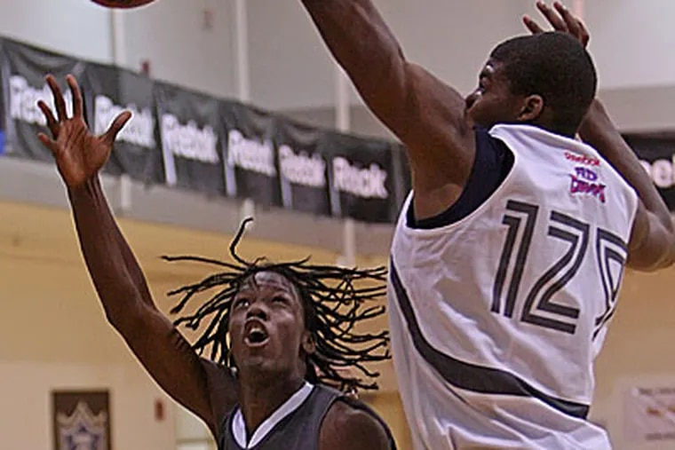 Tyrone Garland, left, works around Keith Coleman, right, to score during their game Thursday afternoon at Philadelphia University. (Michael Bryant / Staff Photographer)