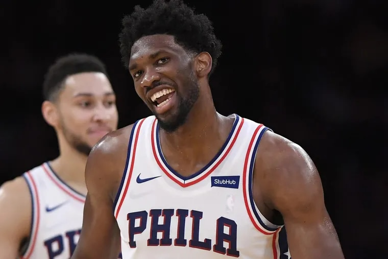Sixers center Joel Embiid (right) smiles after scoring as guard Ben Simmons stands in the background during the second half of an NBA basketball game against the Lakers on Wednesday.