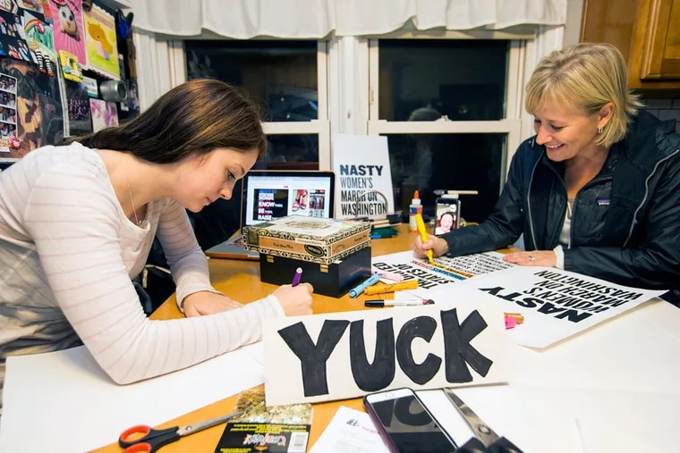 Cait Kinslow (left) and Tina Markoe Kinslow work on signs. Kinslow has organized a group of family and friends to rent a bus and head to the Women's March on Washington on Jan. 21.