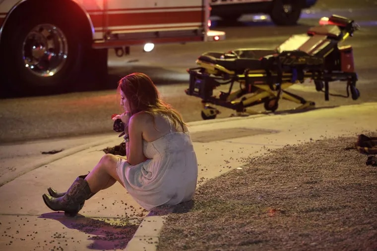 A woman sits on a curb at the scene of the shooting outside  a music festival along the Las Vegas Strip.