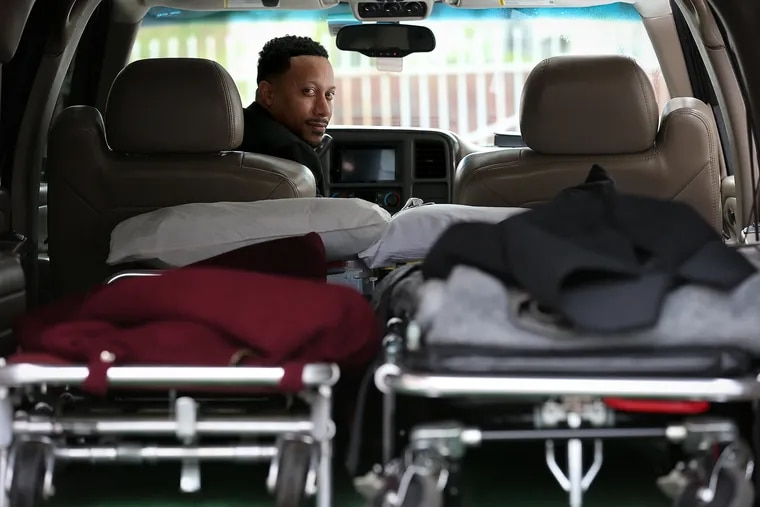 Preston Griffin, who runs First Class Mortuary Transport, inside his vehicle after delivering a body to the Alfonso Cannon Funeral Chapels in Philadelphia.