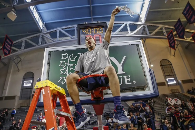 Penn's Darnell Foreman takes a seat atop one of the Palestra's rim, following a Quakers tradition when teams go to the NCAA tournament.