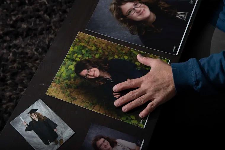Juanita Jones-Wible arranges photos of her daughter Amanda, at her home in Philadelphia.