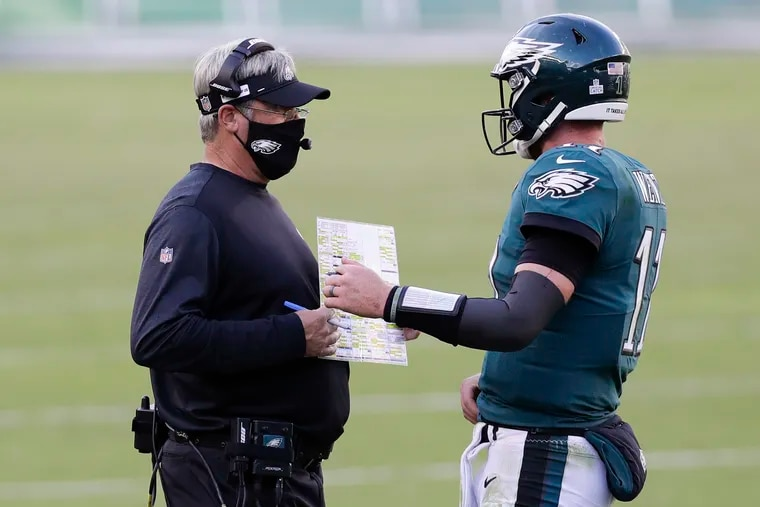 Eagles Head Coach Doug Pederson and quarterback Carson Wentz meet late in the fourth quarter against the Baltimore Ravens on Sunday.