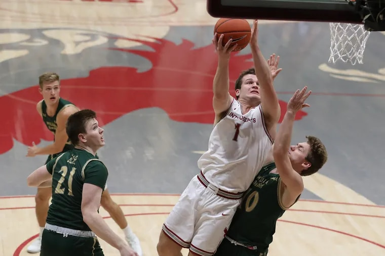 Ryan Daly, center, of St. Joesph's goes up for a shot against Rainers Hermanovskis of William & Mary during the 1st half at Hagan Arena  on Dec. 19, 2019.