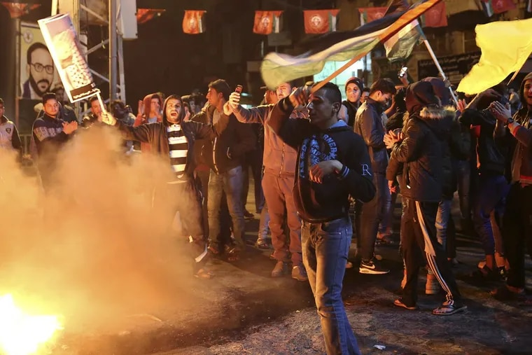 Palestinian protestors burn tires as they wave national flags in Gaza City on Wednesday after President Trump  recognized Jerusalem as Israel's capital.