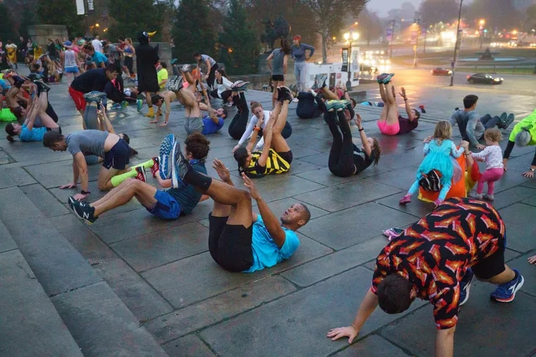 Howard Monroe, turquoise shirt and black shorts front center doing sit up, and Matt Baumann, orange shirt front right doing a push up, participate in the November Project, a free workout, on the steps of the Philadelphia Art Museum, in Philadelphia, October 30,2019.