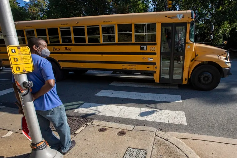 Building engineer Robert Brown doubles as a crossing guard as a bus without students checks in before driving off during morning drop off for students at Wissahickon Charter School , 4700 Wissahickon Ave., in Philadelphia on Friday, Sept. 10, 2021.