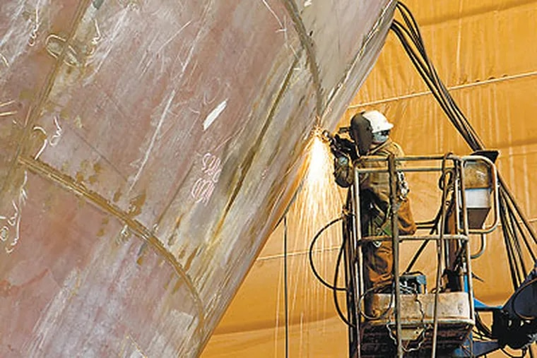 A worker grinds a weld on the bow of a tanker under construction in the yard's Grand Block Shop (Photo: Aker Philadelphia Shipyard)