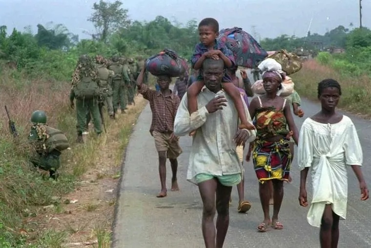 Civilians forced to flee their homes amid fighting during Liberia's first civil war pass West African peacekeeping forces on a road outside of Monrovia in 1995.
