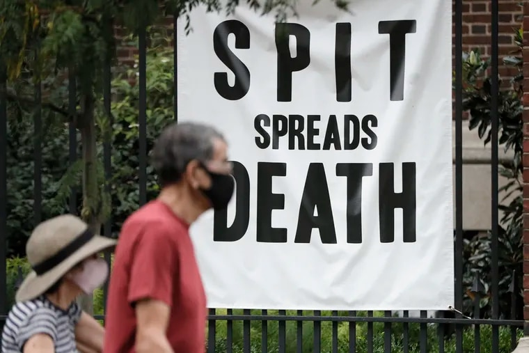 """A couple walks by a sign for """"Spit Spreads Death: The Influenza Pandemic of 1918-19 in Philadelphia"""" an exhibit at the Mütter Museum of the College of Physicians of Philadelphia. Museums are shuttered under new COVID restrictions."""