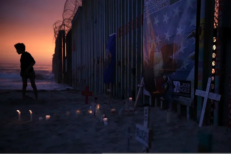 A youth stands by the border fence that separates Mexico from the United States, where candles and crosses stand in memory of migrants who have died during their journey toward the U.S., in Tijuana, Mexico, late Saturday, June 29, 2019. On the border fence at right hangs a cartoon depiction of a news photograph of the bodies of Salvadoran migrant Óscar Alberto Martínez Ramírez and his daughter Valeria, photographed on the banks of the Rio Grande between Matamoros, Mexico, and Brownsville, Texas, after they drowned on Sunday, June 23.