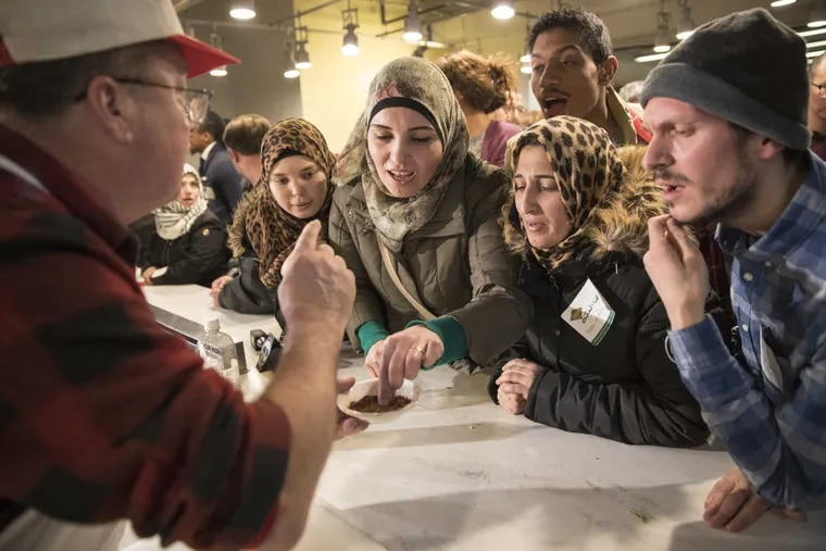Syrian refugee Abeer Bdaiwi samples chipotle that chef Jack McDavid (left) used.