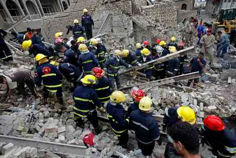 Rescuers search the site of a bomb attack at the temporary headquarters of the Finance Ministry, which was destroyed in an August bombing. Yesterday's bombings raised new questions on next year's elections.