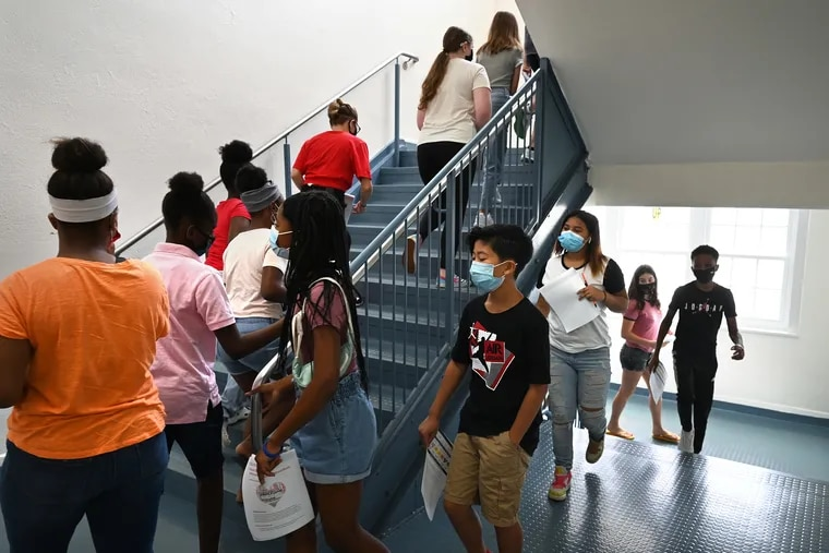At Woodbury High School in South Jersey, junior high school students wearing masks tour the building during an orientation in August. In Pennsylvania, a Chester County school district's masking requirements remain after a federal judge ruled against parents challenging Tredyffrin/Easttown's mandate.