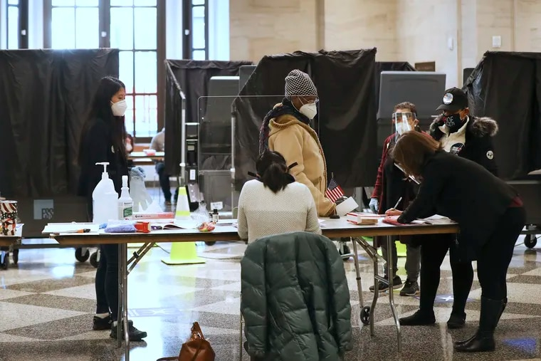Poll workers assist voters inside the American Museum of the Revolution in Old City, Philadelphia, on Tuesday.
