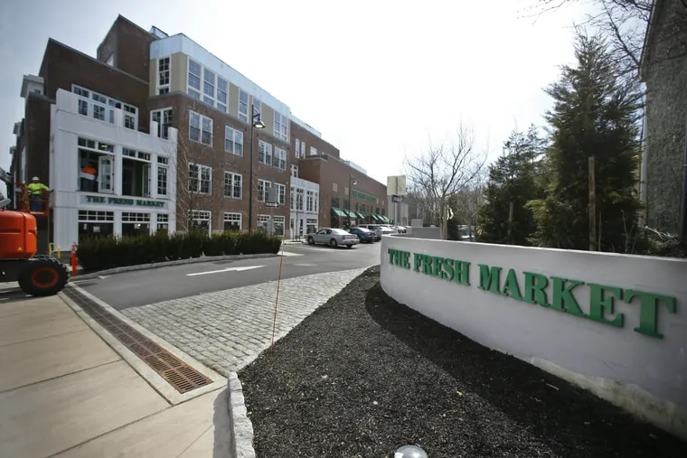 The landscaped driveway and placement of the supermarket off the street are among the design features that helped One West integrate itself into the surroundings in Chestnut Hill. This approach could succeed in other traditional neighborhoods.
