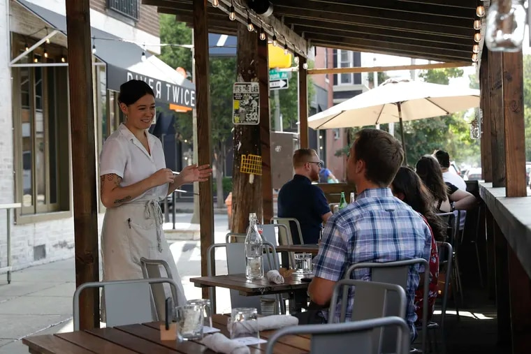 Server Maggie Cook (left) talks to diners in the outdoor dining area at River Twice along East Passyunk Avenue in July.