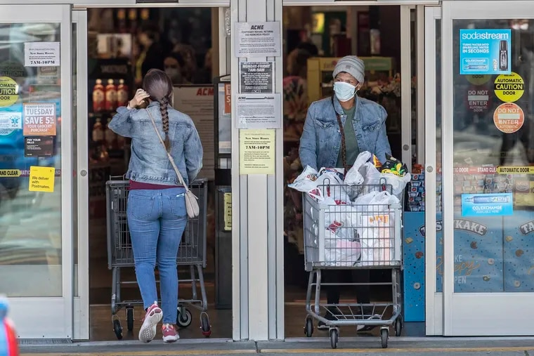 Both customers, entering, left, and exiting, right, the Acme grocery store on Ridge Avenue in Roxborough were wearing masks as a personal protection against the spread of the coronavirus on Sunday morning April 19, 2020.  ACME's parent is seeing robust sales during the pandemic, encouraging its plan to sell shares to the public.