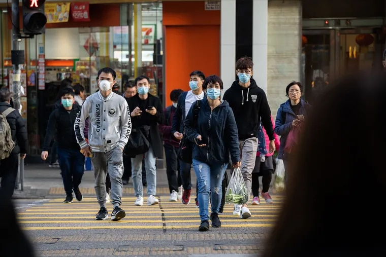 Residents wear surgical masks while crossing the road in order to prevent the spread of the Wuhan corona virus on Thursday in Hong Kong.