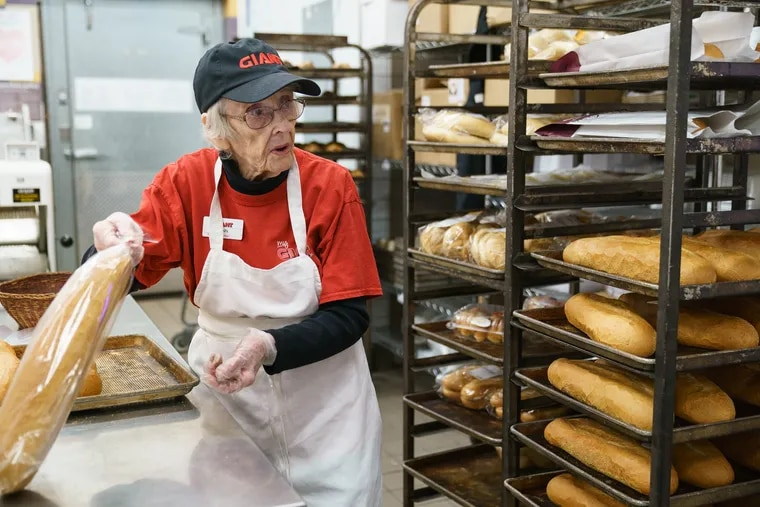 Giant Food stores associate Wynnifred Franklin, 94, bags bread in the bakery of the Audubon store.