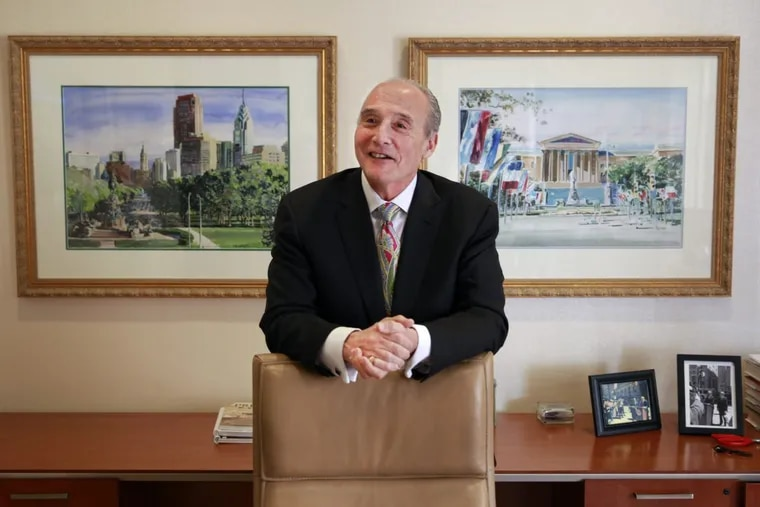 Joseph Coradino, CEO of PREIT, stands in his office with images of Philadelphia surrounding him.