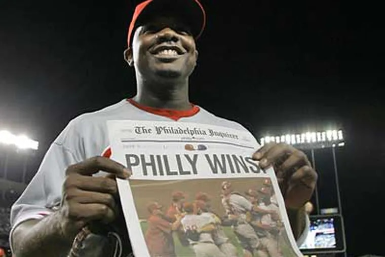 Ryan Howard holds up a copy of The Philadelphia Inquirer celebrating the Phillies' win in Game 5 of the NLCS and a spot in the World Series. (Yong Kim / Staff Photographer)
