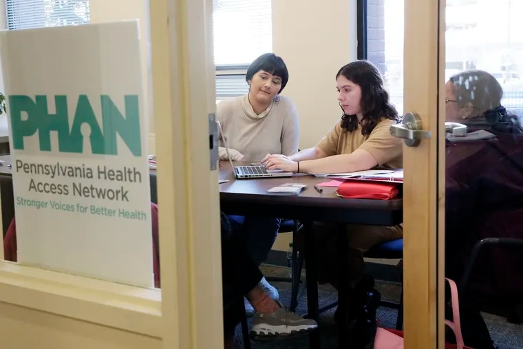 Quaker Voluntary Service Fellow Sarah Bluett (left) and Community Engagement Specialist Joanna Rosenhein (middle) help a client review their health coverage options and sign up for a plan on the 2020 enrollment period's first day of open enrollment at The Friends Center in Phila., Pa. on November 1, 2019.