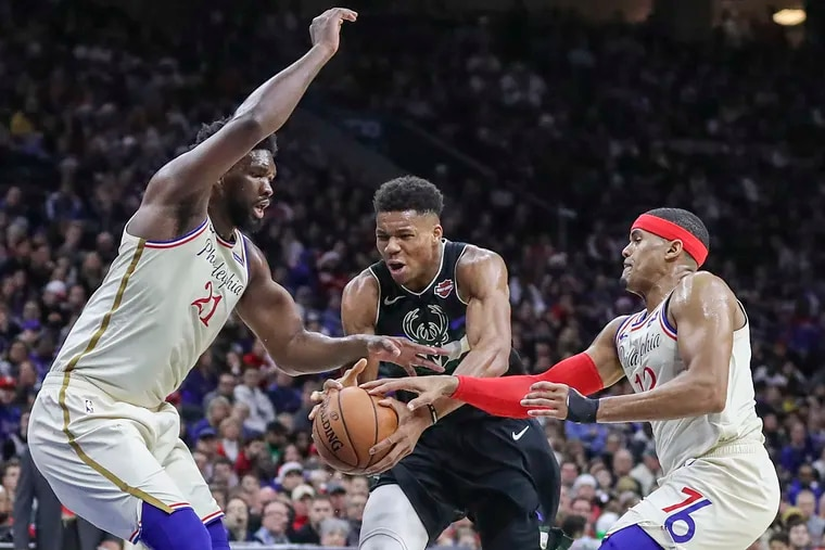 Giannis Antetokounmpo drives to the basket against Joel Embiid (21) and Tobias Harris in the second quarter of a game at the Wells Fargo Center  on Wednesday.