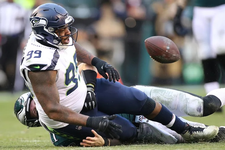 Seahawks defensive tackle Quinton Jefferson falls on Eagles quarterback Carson Wentz's throwing hand as Wentz tries to tackle him after the Eagles fumbled in the third quarter.